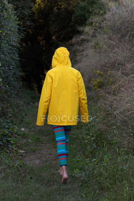 Opinião traseira a fêmea descalça nova no revestimento amarelo que anda nas madeiras sozinho — Fotografia de Stock