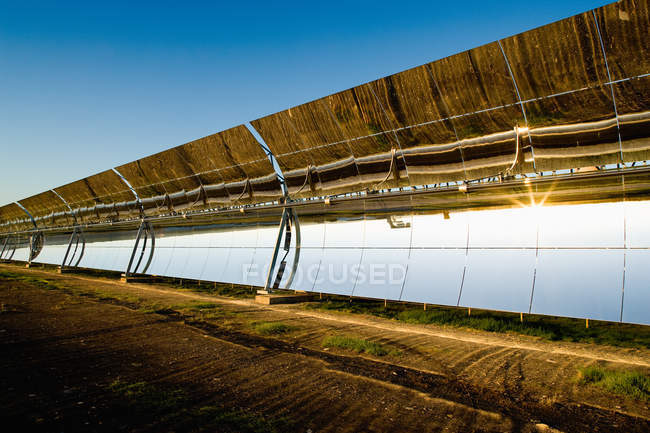 Surface of modern solar panels reflecting bright sun on photovoltaic power station against cloudless blue sky — Stock Photo