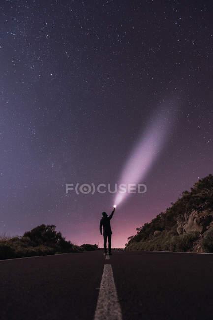 Voyageur debout avec torche à la nuit étoilée — Photo de stock