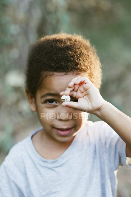 Dulce niño afroamericano mirando a la cámara y demostrando una pequeña concha marina mientras está de pie sobre un fondo borroso en el campo - foto de stock