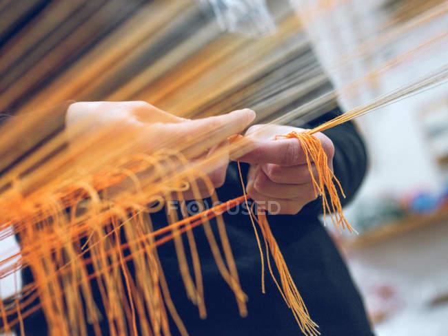 Close-up de mãos humanas segurando fios no tear — Fotografia de Stock