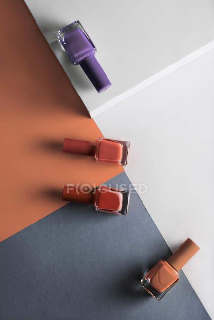 Багатокольорові нігті полірують на кольоровому геометричному фоні. — стокове фото
