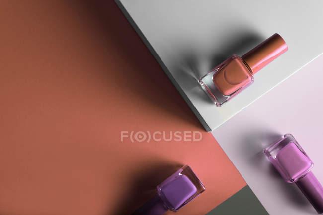 Разноцветные лаки для ногтей на фоне геометрических узоров — стоковое фото