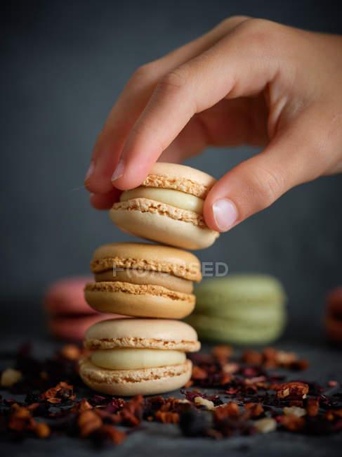 Mão de pessoa que toma macaron de uma pilha no fundo cinza com frutos secados — Fotografia de Stock