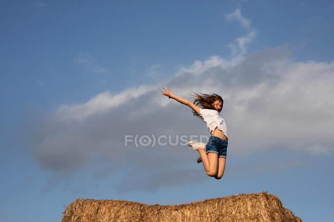 Da vista lateral abaixo da fêmea Charming nova com o cabelo marrom que salta na bala do feno — Fotografia de Stock
