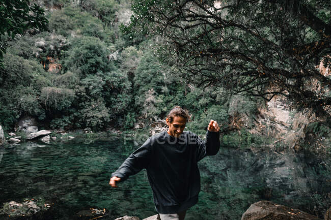 Man standing near calm pond in forest — Stock Photo