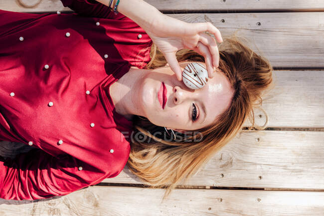 Donna guardando attraverso buco ciambelle su picnic — Foto stock