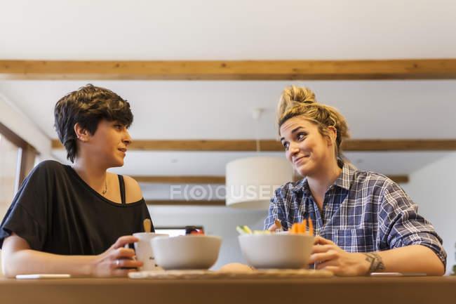 Duas mulheres bonitas e jovens tomando café da manhã em casa e se divertindo — Fotografia de Stock
