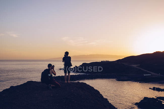 Back view of traveling people standing on top of cliff and taking photo of beautiful sundown above coast — Stock Photo