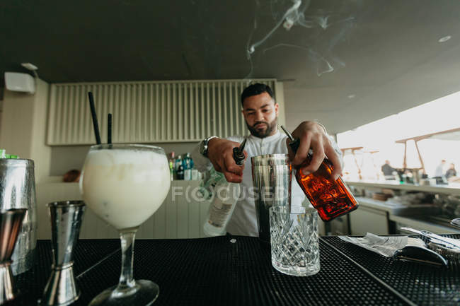 Bartender pouring alcoholic drinks to shaker in bar — Stock Photo