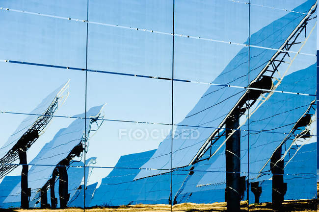 Відображення сучасних сонячних панелей на скляній стіні в сонячний день на фотоелектричних електростанції в сільській місцевості — стокове фото