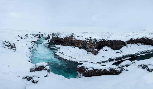 View of powerful stream of water and cliff covered with snow, Godafoss waterfall, Iceland — Foto stock