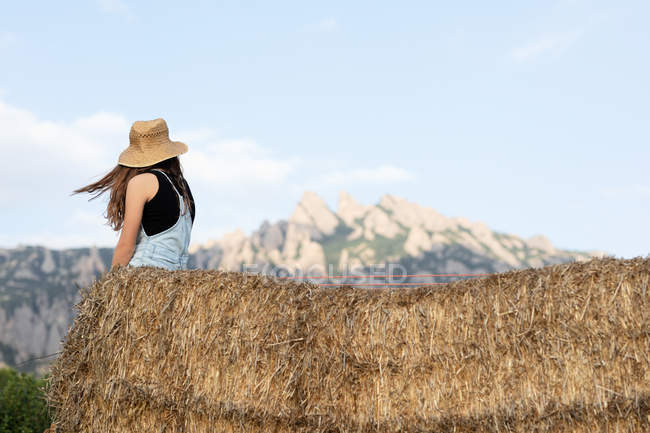 Anonymous young beautiful female in casual clothes and hat sitting on bale of hay — Stock Photo