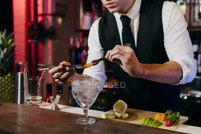 Crop anonymous young elegant barman working behind a bar counter mixing drinks with fruits — Stock Photo