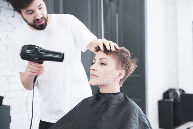 Hairdresser drying hair to woman — Photo de stock