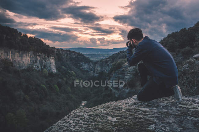 Man with photo camera sitting on hill mountain with magnificent sunset — Stock Photo