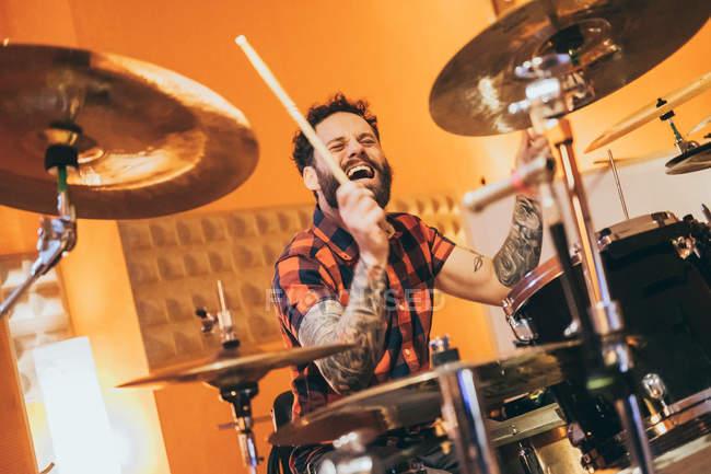 Доросла людина сидить у музичній студії і грає на барабанах. — стокове фото