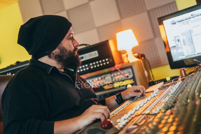 Музыкант, работающий во время игры на эквалайзере в студии — стоковое фото