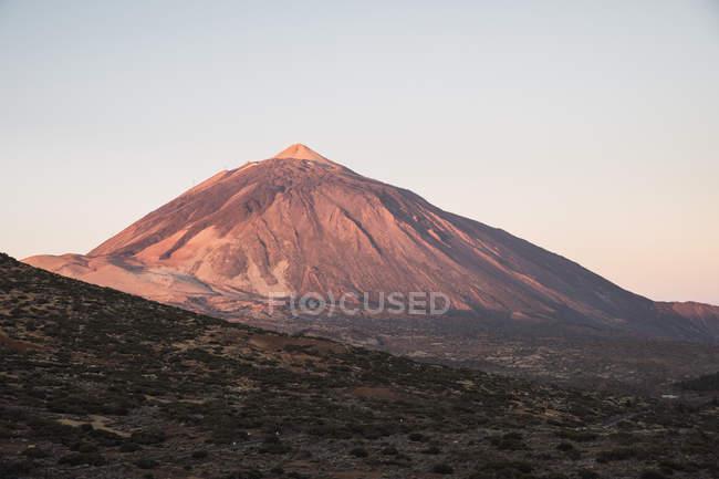 Mountain peak in desert valley at sunset — Stock Photo