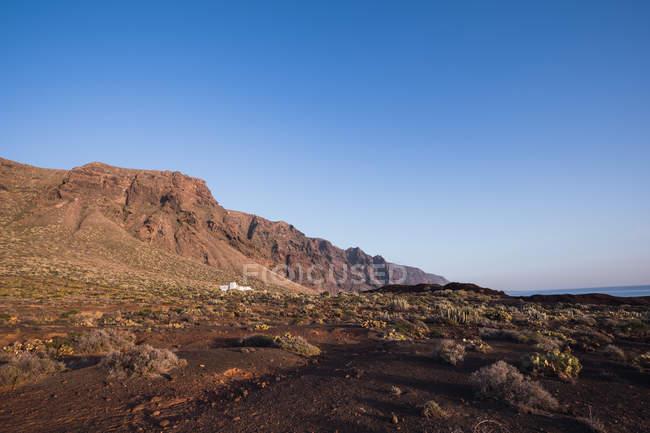 Paisagem estéril da montanha rochosa no fundo do céu azul — Fotografia de Stock