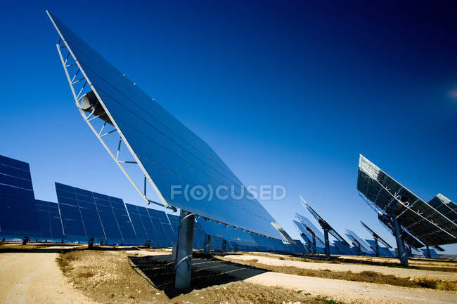 Modern solar panels installed in field against cloudless blue sky in photovoltaic power station — Stock Photo