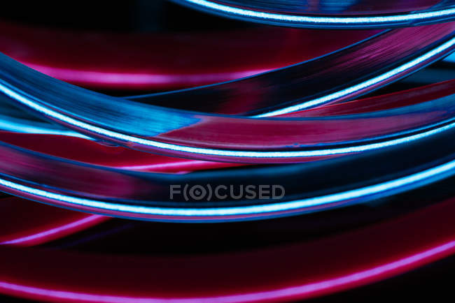 Stack of neon light tubes on black background — Stock Photo