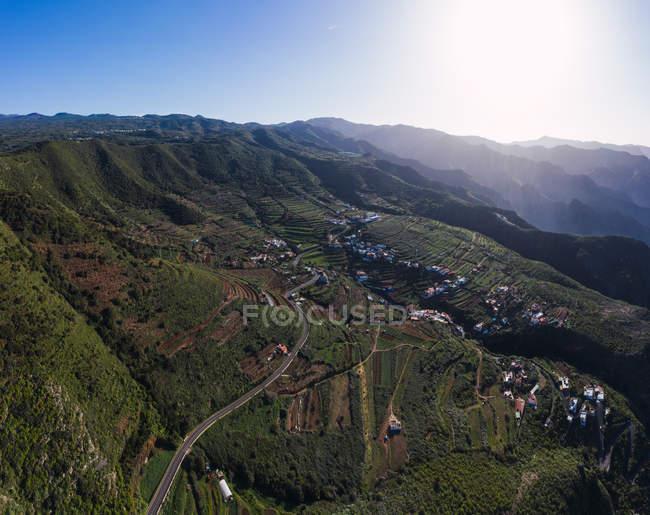Vista aerea della strada curva attraverso il paesaggio montano in luce solare brillante — Foto stock