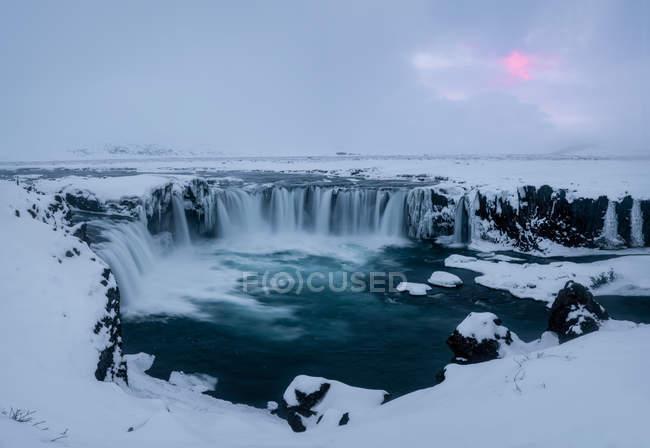 Vista della potente cascata Godafoss e scogliere coperte di neve in Islanda — Foto stock