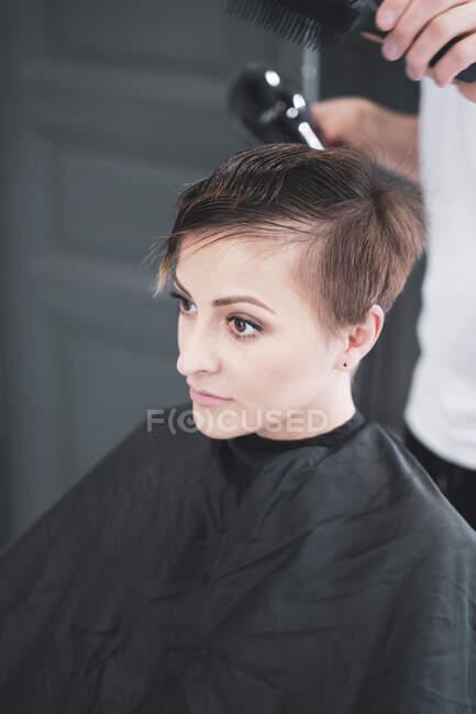 Parrucchiere asciugando capelli a donna — Foto stock