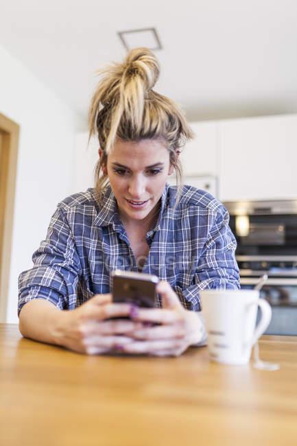 Вродлива і молода жінка снідають вдома, розважаються і розмовляють з розумним телефоном. — стокове фото
