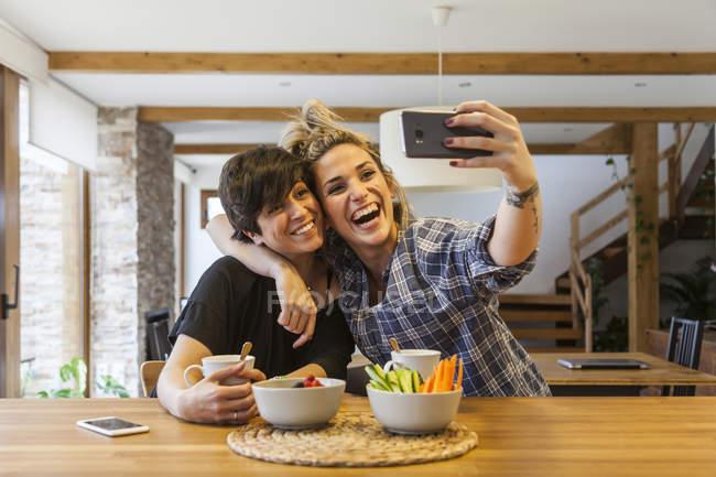 Две красивые молодые женщины, завтракающие дома и веселящиеся, делают автофото со смартфоном — стоковое фото