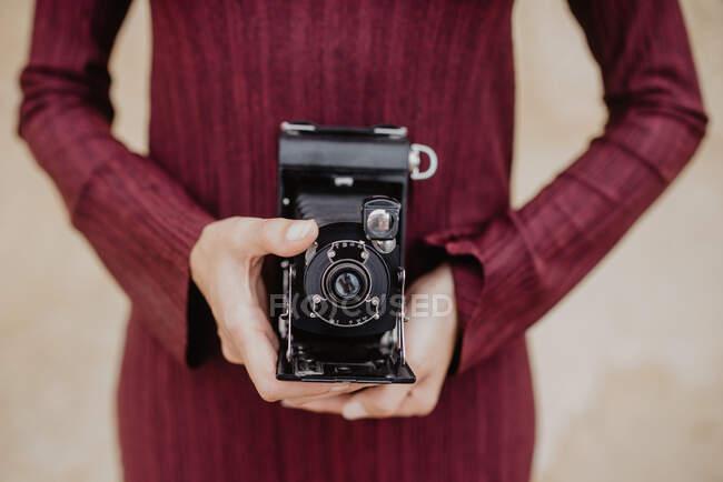 Анонимная женщина в стильном платье с ретро-камерой, стоящая возле потрепанной стены — стоковое фото