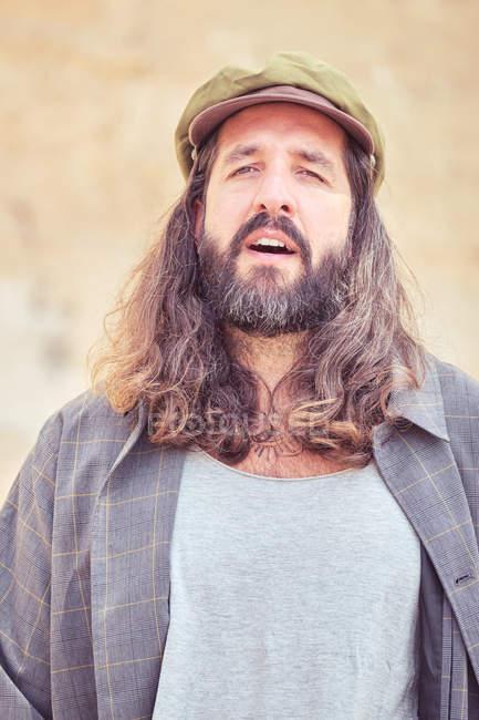 Стильный бородатый мужчина с длинными волосами смотрит в камеру — стоковое фото