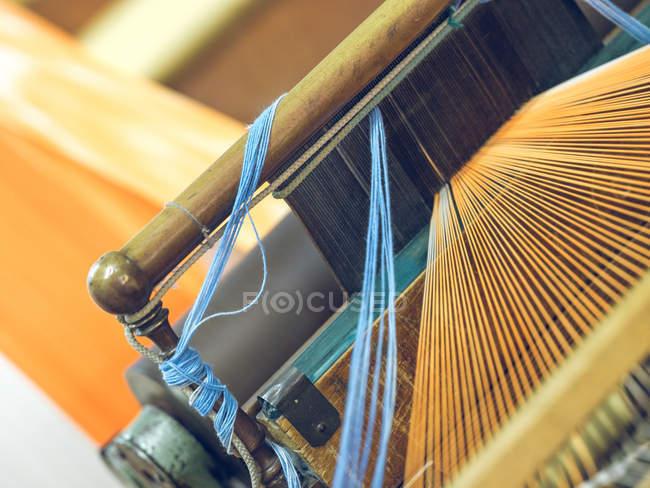Close-up das linhas azuis e alaranjadas no tear — Fotografia de Stock