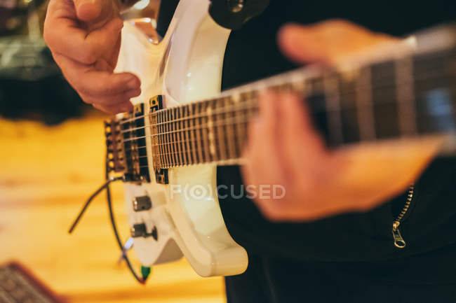Closeup of male hands in music studio playing guitar — Stock Photo