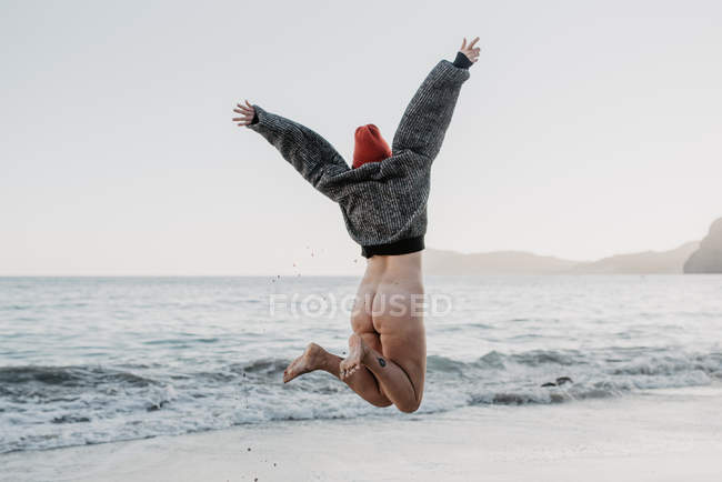 Back view of young woman with naked buttocks raising hands enjoying freedom while jumping near waving sea in nature — Stock Photo