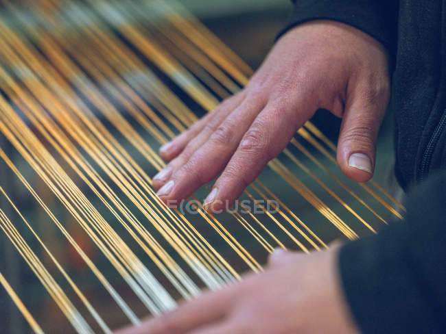 Hands of weaver touching thread on loom — Stock Photo