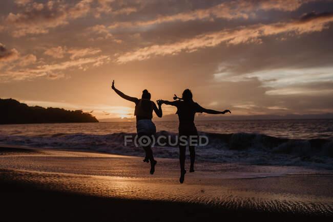 Силуэты анонимных подруг, держащихся за руки и прыгающих к морю на фоне облачного заката — стоковое фото