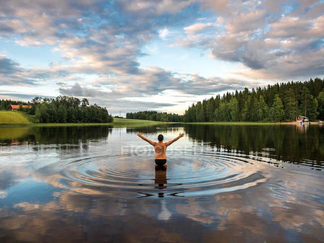 Vista posteriore dell'uomo in piedi nel lago e braccia aperte mentre si gode il paesaggio con foreste e case in Finlandia — Foto stock