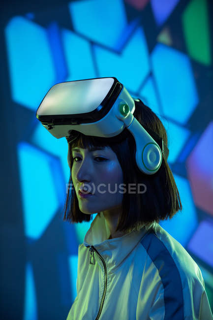 Young woman with virtual reality goggles looking away in neon light — Stock Photo
