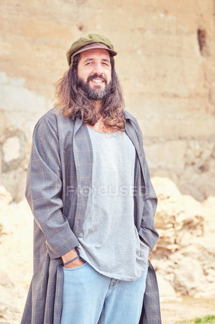 Hombre barbudo elegante con el pelo largo en la calle posando y mirando a la cámara - foto de stock