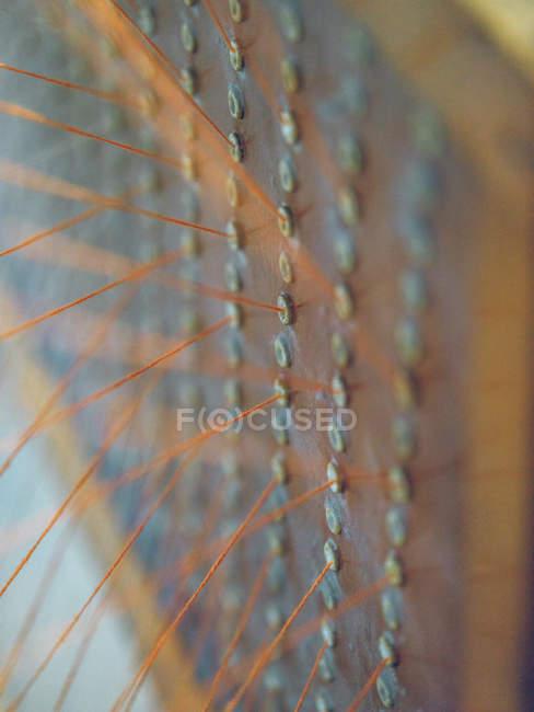 Close-up das linhas alaranjadas no tear na fábrica — Fotografia de Stock