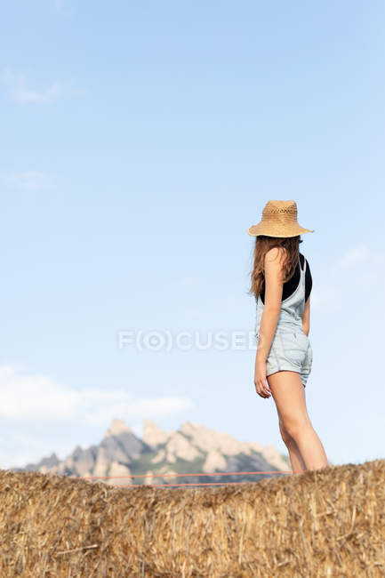 Anonymous young beautiful female in casual clothes and hat standing on bale of hay — Stock Photo