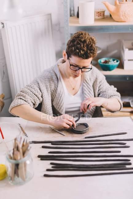 Женщина гончар с помощью глиняных полос, чтобы сформировать горшок на workbench в профессиональной мастерской — стоковое фото