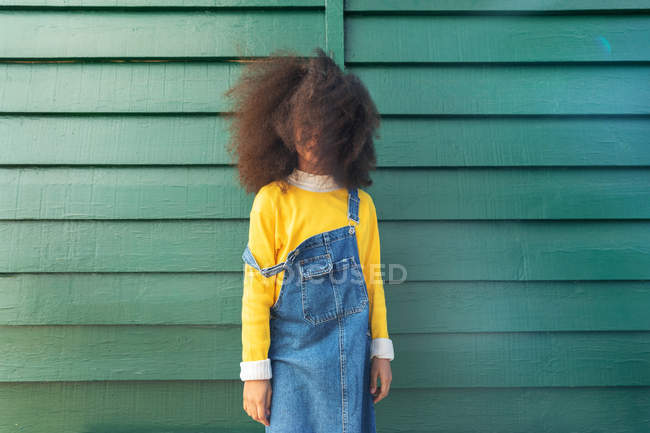 African american girl standing near green wall — Stock Photo