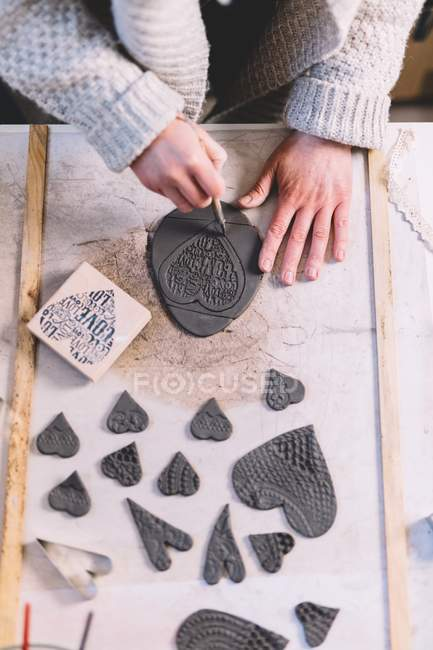 Woman making ornamental hearts from soft clay on table in potter workshop — Stock Photo