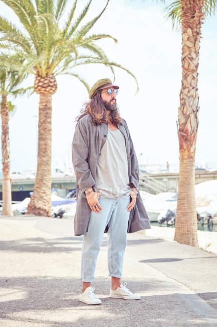Hombre barbudo elegante con pelo largo caminando por la calle con gafas de sol cerca de la palmera - foto de stock