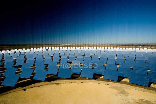 Moderni pannelli solari che riflettono i raggi luminosi contro il cielo blu senza nuvole nella giornata di sole sulla centrale fotovoltaica — Foto stock