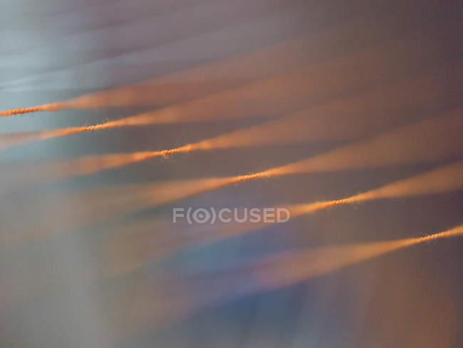 Close-up de linhas alaranjadas no tear borrado — Fotografia de Stock