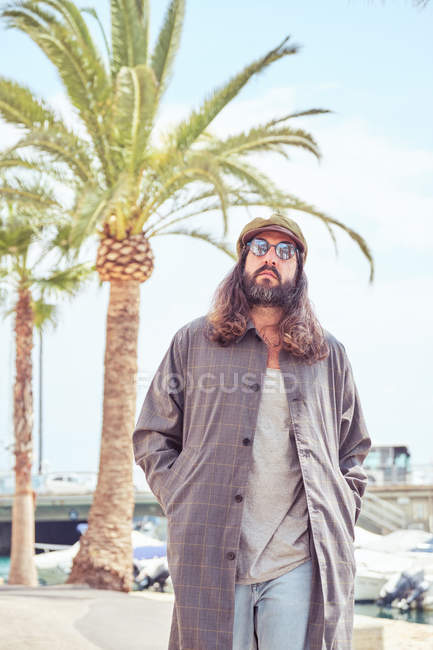 Stylish bearded man with long hair walking on street with sunglasses near palm tree — Stock Photo